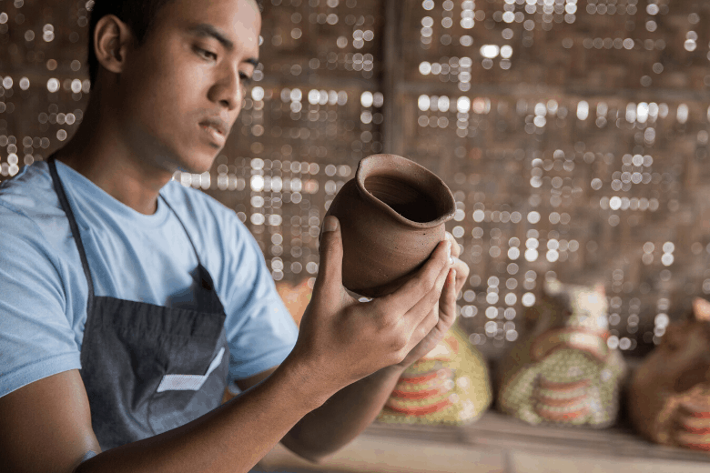 man inspecting pottery