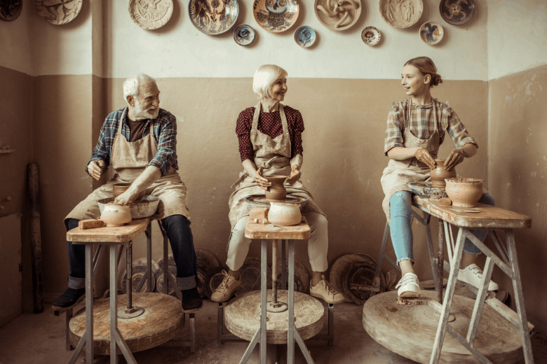 three people making pottery
