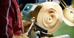 man turning wood on a lathe